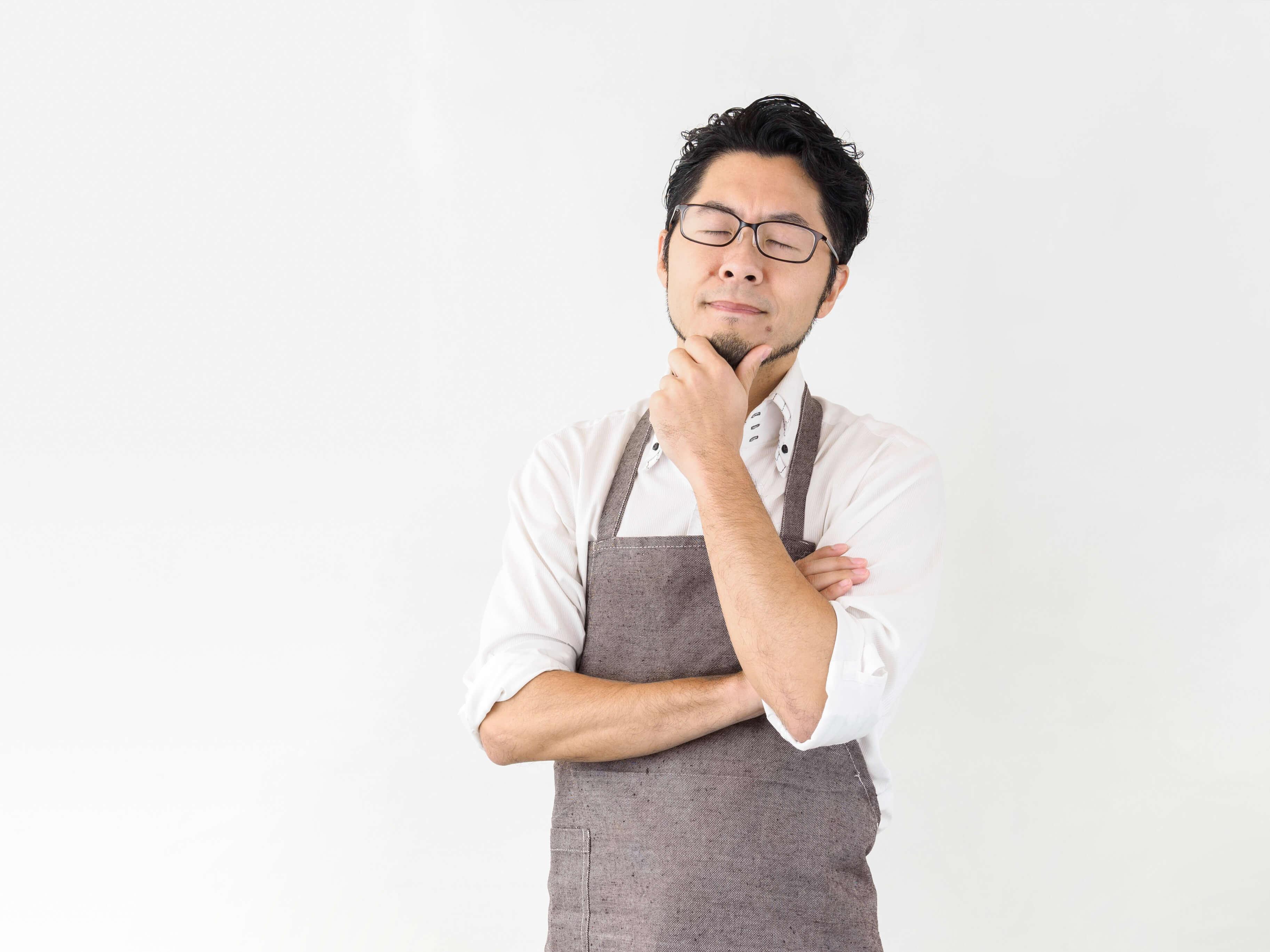 白背景の自宅にて家事に悩む日本人男性